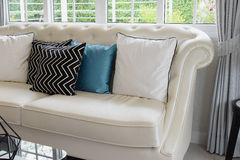 White and blue pillows on a white leather couch Royalty Free Stock Photo