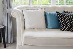 White and blue pillows on a white leather couch in vintage living room Stock Image