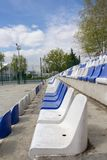White and blue plastic empty stadium seats in arena. At a sunny day royalty free stock image