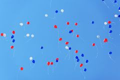 White, blue and red baloons flying high in clear blue sky Royalty Free Stock Photography