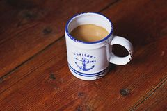White and Blue Sailor Ceramic Coffee Mug on Brown Wooden Surface Royalty Free Stock Image