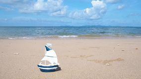 Small boat toy on summer beach background. White and blue small boat toy on sand with copy space. Vacation on summer beach background concept stock footage