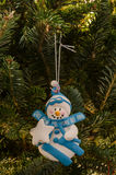 White and Blue Snowman Ornament. A clay Christmas ornament depicts a white snowman with blue clothing holding a white star stock photo
