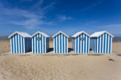 White & blue striped beach houses on a sunny beach Royalty Free Stock Images
