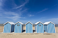 White & blue striped beach houses on a sunny beach Stock Photography