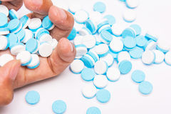 White and blue tablets pills on hand Stock Photos