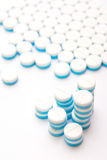 White and blue tablets pills on white background Stock Image