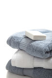 White and blue towels with soap on white Royalty Free Stock Image