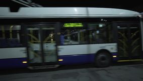 White and blue trolleybus drive in night city road behind the bridge. Riga town stock video footage