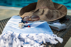 A white and blue Turkish towel, sunglasses, bikini and straw hat on rattan lounger with blue swimming pool as background. Stock Photography