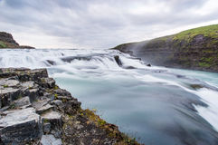 White and Blue Waterfalls Near Green and Gray Rocks Under the Cloudy Sky Stock Photos