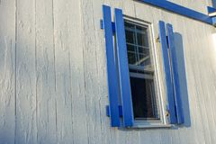 White and blue wood home with blue window shades with sunrise sunset lighting. Window with open blue outdoor sutters on a white house stock photography
