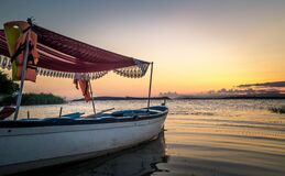 White and Blue Wooden Boat on Body of Water Under Orange Sunset Royalty Free Stock Image