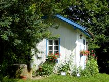 White and blue wooden retro hut in a flowering garden stock photos