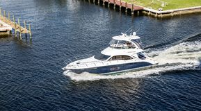White and Blue Yacht Motoring the Intracoastal Royalty Free Stock Image