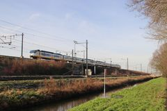 White, blue and yellow local commuter train on track at Zwijndrecht the Netherlands. White, blue and yellow local commuter train on track at Zwijndrecht the stock photos