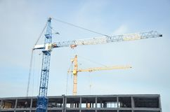 White blue and yellow tower cranes towering above a concrete building under construction against a blue sky royalty free stock image