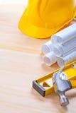 White blueprints construction level yellow helmet Royalty Free Stock Image