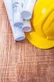 White blueprints and yellow helmet on wooden board Royalty Free Stock Photo
