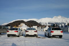 White BMW. Three white BMW cars exhibited at a horse race on the frozen lake of St Moritz, Switzerland: (from right to left:) 5 type hatchback, 6 type and 3 type Royalty Free Stock Images