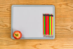 White board with colorful pencils and apple on desktop Royalty Free Stock Photo