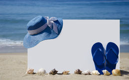 White board with flip-flops and hat on sandy beach Stock Images