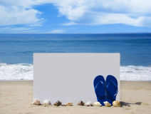 White board with flip-flops on sandy beach. White board with flip-flops and seashells on sandy beach Royalty Free Stock Images