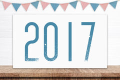 2017 on white board and party flags hanging on white wood backgr. Ound, new year concept Stock Images