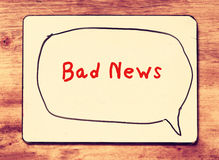 White board with the phrase bad news written on it, over wooden background. filtered image with retro effect. Royalty Free Stock Photography