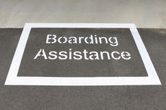 White 'boarding assistance' zone on a train station platform Stock Photos