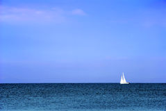 White boat. Little white boat sailing of the blue sky Stock Image