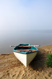 White boat. White empty boat on sand shore on misty morning over Lipno reservoir, Czech Republic Royalty Free Stock Images