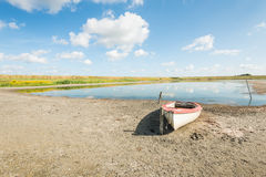 White boat on the banks of a natural pond Stock Image