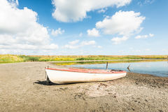 White boat on the banks of a natural pond Stock Photos