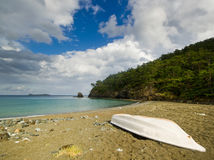 White boat on the beach with forest and sky Royalty Free Stock Image