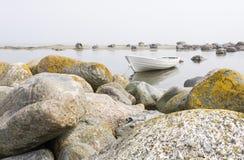 White boat behind large stones Royalty Free Stock Photo