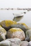 White boat behind large stones Stock Photos