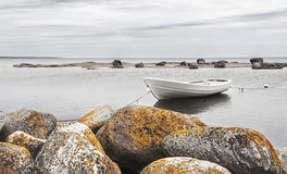 White boat behind rocks Stock Images