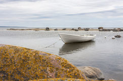 White boat behind rocks Stock Photography