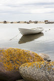 White boat behind rocks Royalty Free Stock Images