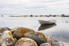 White boat behind rocks Stock Photo