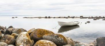 White boat behind rocks Stock Image