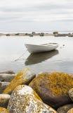 White boat behind rocks Royalty Free Stock Image