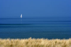 White Boat on Blue Sea. Watched from the beach Stock Photos