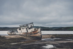 White Boat in Brown Sand Low Tide Royalty Free Stock Photos