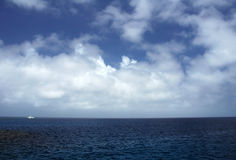 White boat in distance. Ocean scenery, blue sky with clouds, white boat in distance, location: Great Barrier Reef, near Cairns Royalty Free Stock Photo