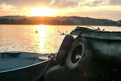 White Boat on Dock Near Two Auto Tires during Sunset Royalty Free Stock Image