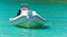 White boat at emerald green sea water near small uninhabited island in Sithonia Royalty Free Stock Images