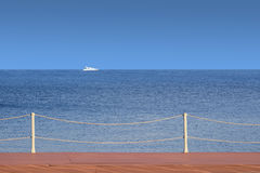 White boat float far on the sea horizon view from the wooden pier in cloudless day. White motor yacht float from left to right far on the sea horizon view from Royalty Free Stock Photography