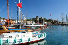 White boat in the harbor of Bodrum with St. Peter Castle in the royalty free stock photo